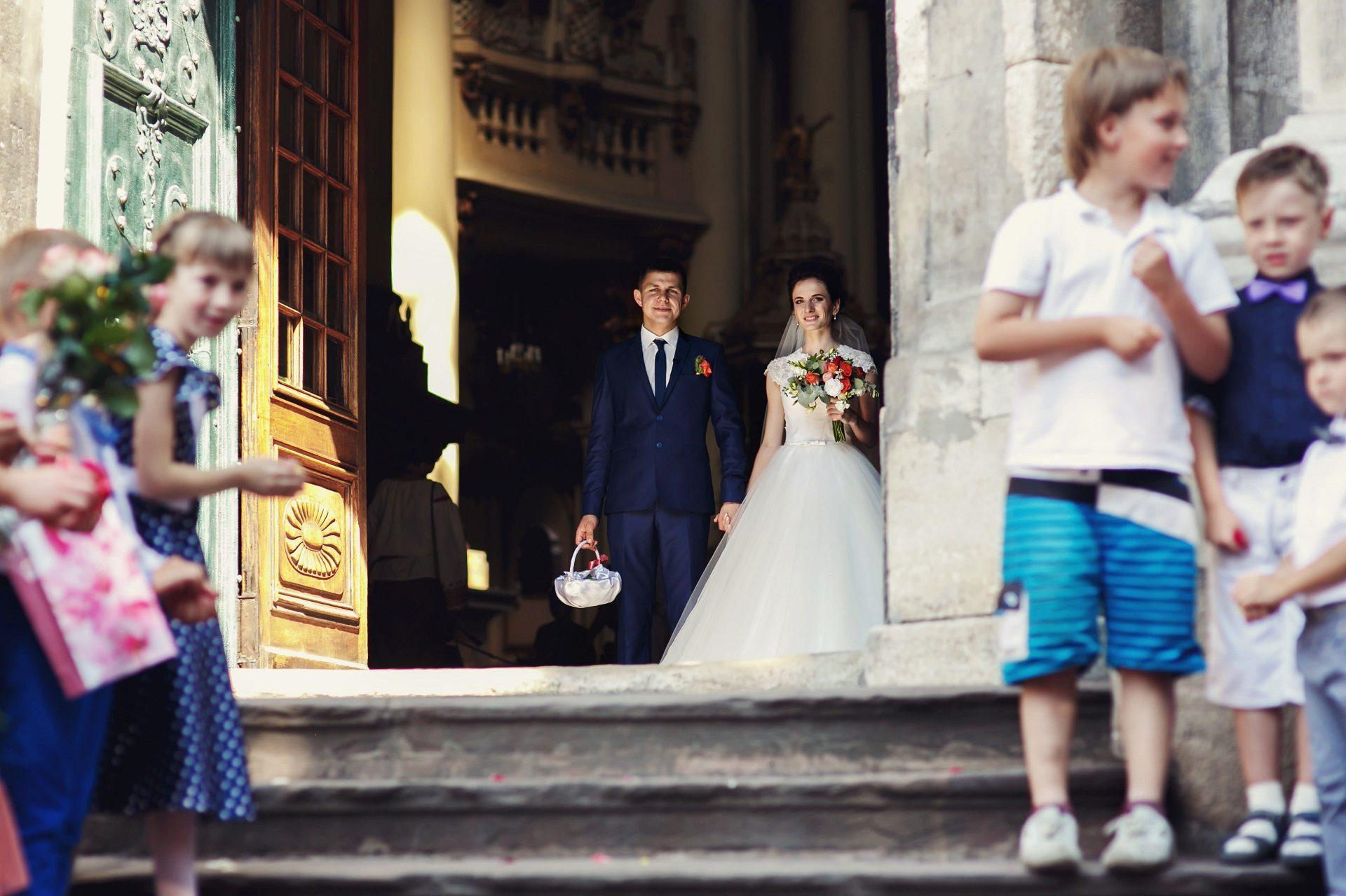 Para młoda wychodząca z kościoła po ślubie z dziećmi w tle