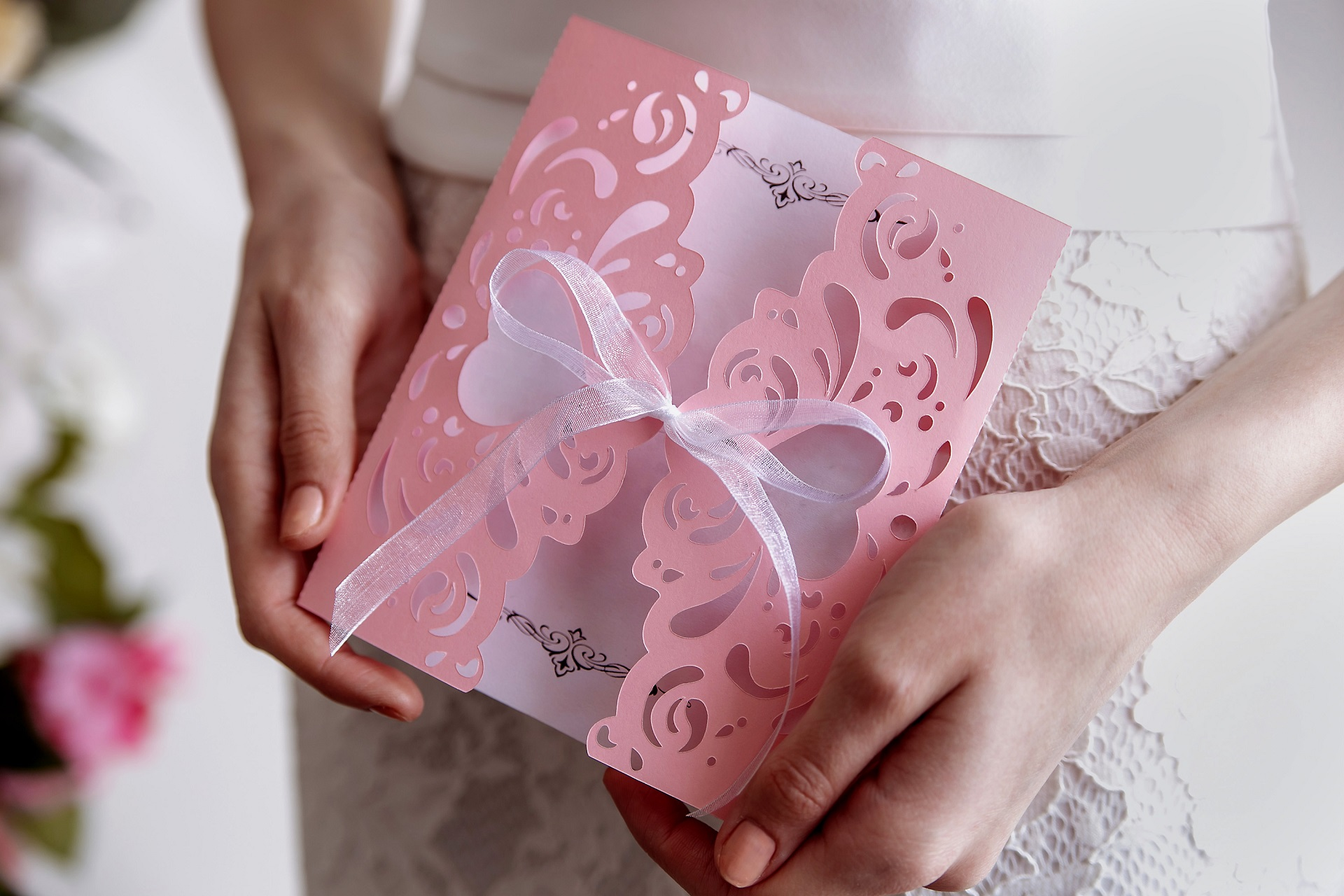 panna młoda trzyma różowe zaproszenie ślubne wycinane laserowo