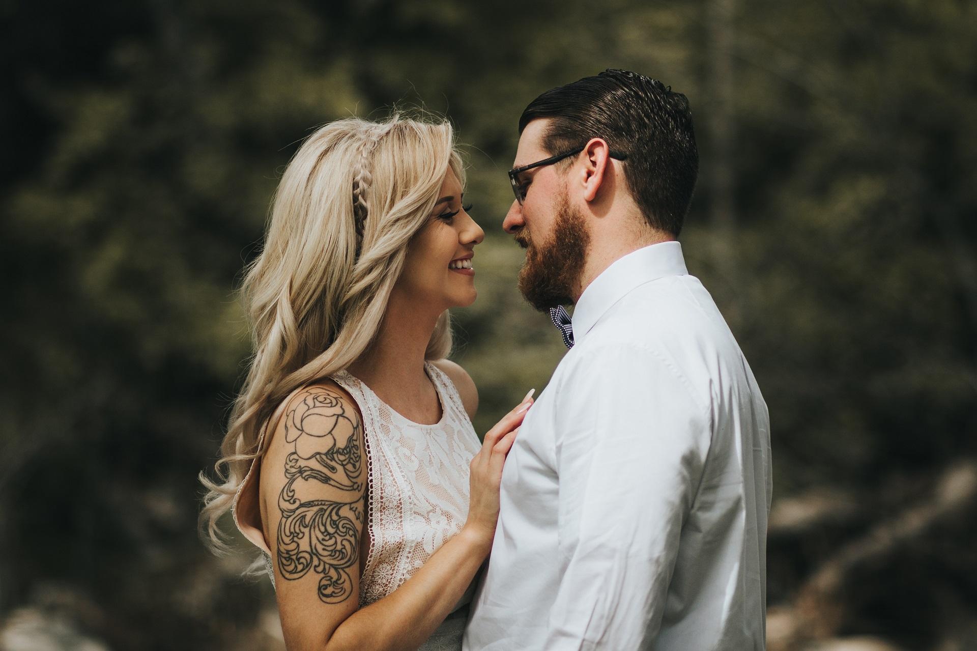 Para Młoda patrząca się na siebie, Panna Młoda z tatuażem na ręku, Panna Młoda z długimi rozpuszczonymi blond włosami