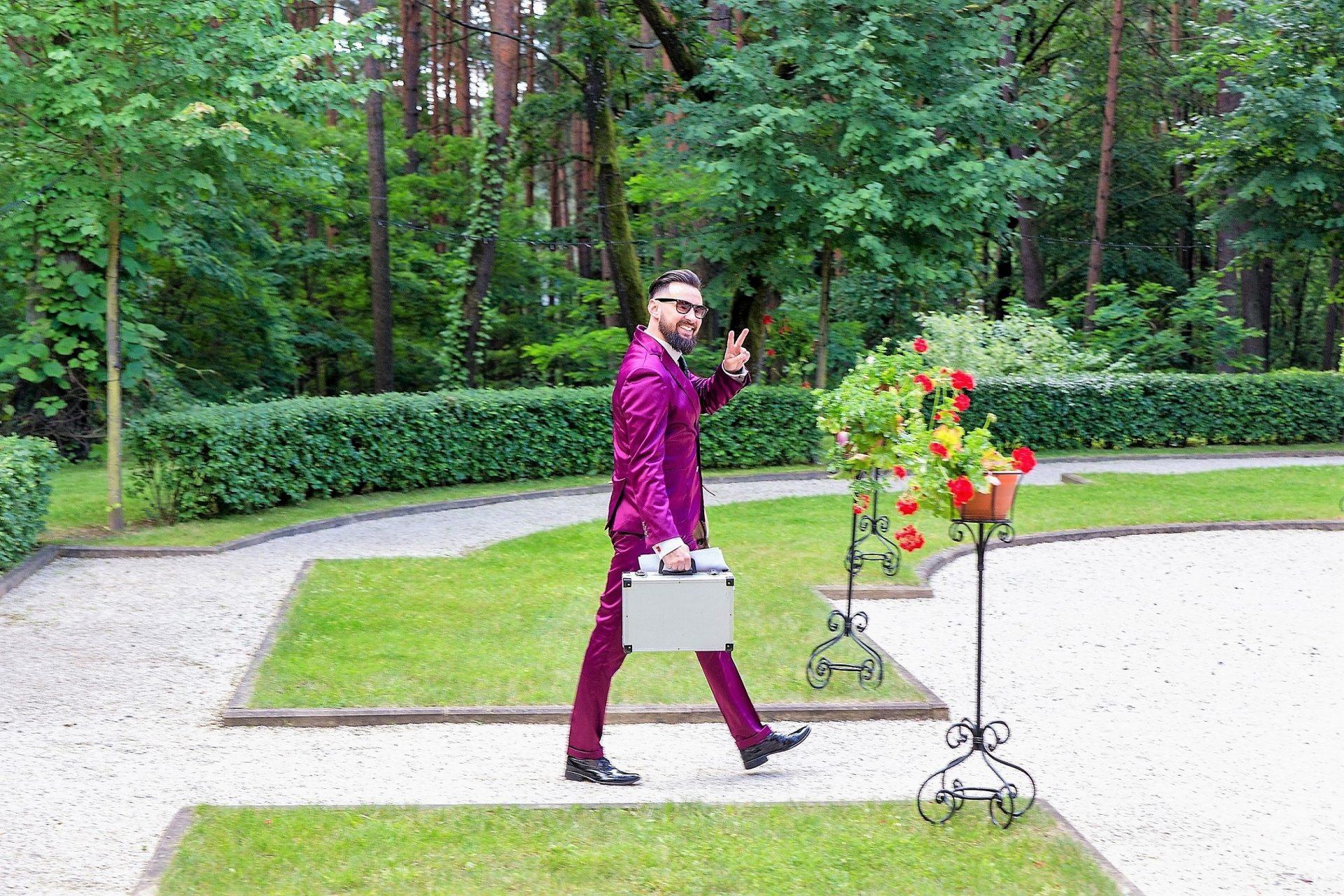Vodzirej przed salą weselną, mężczyzna w fioletowym garniturze , mężczyzna z teczką w dłoni