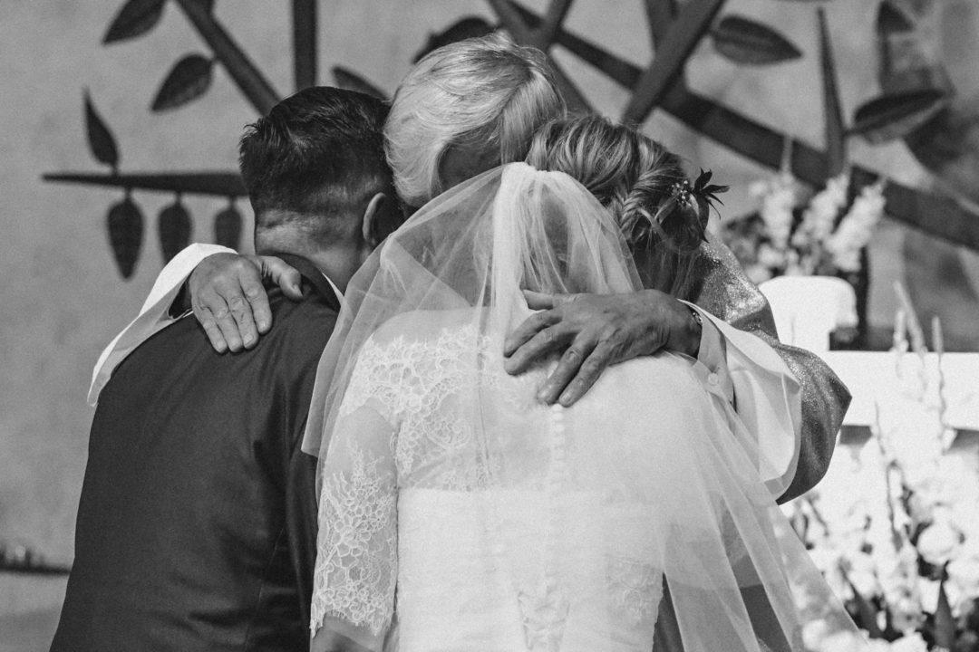 Mama przytulająca Parę Młodą w kościele, Para Młoda w kościele