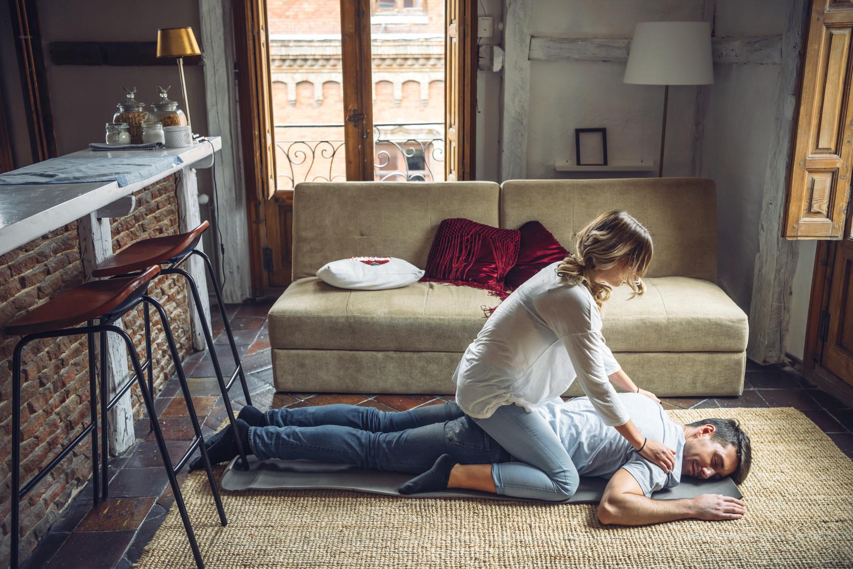 Żona masująca plecy męża leżącego na podłodze