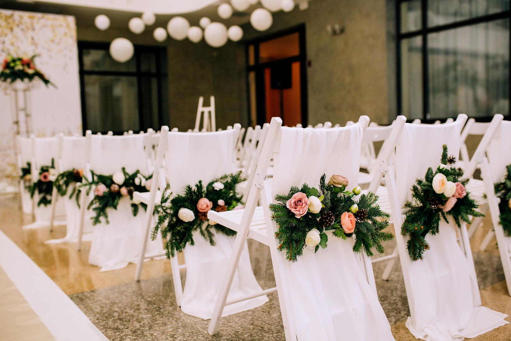 Białe krzesła z kwiatkami  na sal weselnej