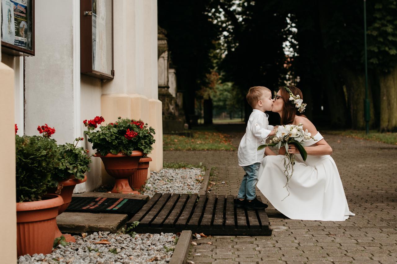 Panna Młoda z bukietem kwiatów i dzieckiem przed salą weselną